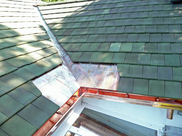Copper flashing installed in roof valley to prevent ice dam leaks.